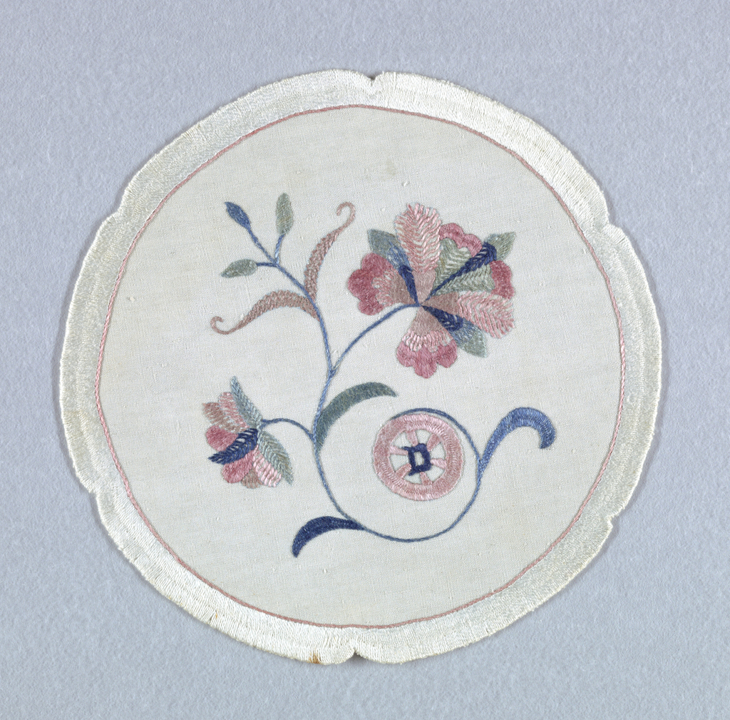 "Round white linen doiley with a notched edge, embroidered in white with a pink border. In the center, a curving stem bearing one large and one small blossom embroidered in muted blues, greens, and pinks.  A signature ""D"" is embroidered within a pink wheel."