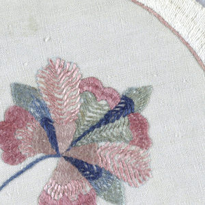 """Round white linen doiley with a notched edge, embroidered in white with a pink border. In the center, a curving stem bearing one large and one small blossom embroidered in muted blues, greens, and pinks.  A signature """"D"""" is embroidered within a pink wheel."""