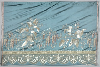 Small panel of blue-green satin with border design embroidered with white, blue, yellow and orchid silks; green, white and orchid chenille; with white satin and net appliqué. Pattern of wisteria and large pointed leaves with lower bands of arabesques.