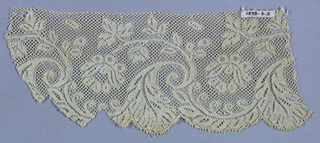 Machine-made border of Valenciennes type lace; floral pattern with scallops on one edge.