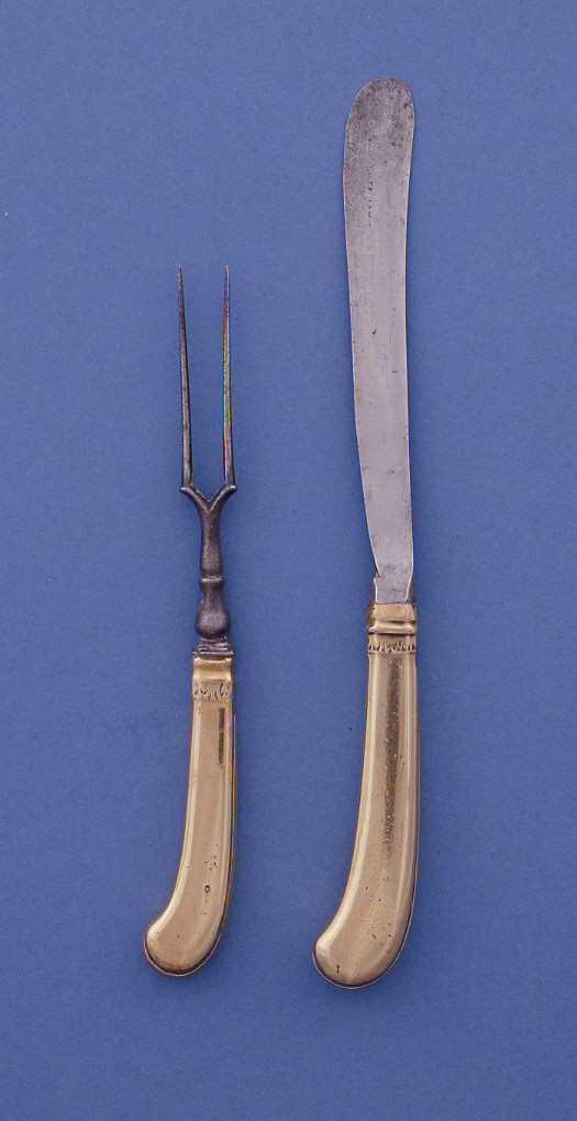 Two tines fork with  V-shaped join, baluster-shaped neck. Flat pistol-shaped brass handles with engraved decoration of stylized leaves near the neck. Decorative bands on the side of the handle.