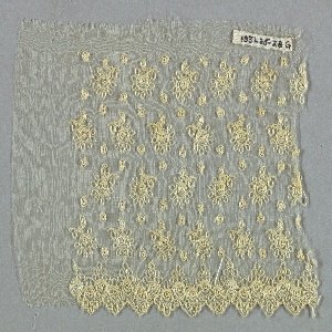 Transparent substrate embroidered with white thread with alternating rows of single flowers with stems. Scalloped border with small rosettes surrounded by curlicues.
