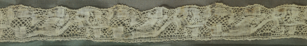 """Lace fragment with a loosely-woven pattern of leaf motifs in a type of rose ground called """"fond à la vierge."""" Fragment is mounted on a fabric-covered board and framed behind glass. Frame is natural wood."""