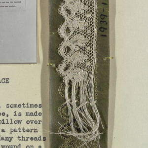 Green paper with pattern marked in pinholes. Narrow band of lace with inserted thread bundles, leaf and circle motif.