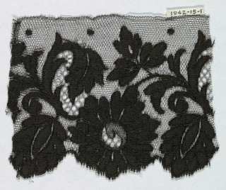 Black Spanish blonde lace with handrun pattern of flowers and leaves on machine ground.