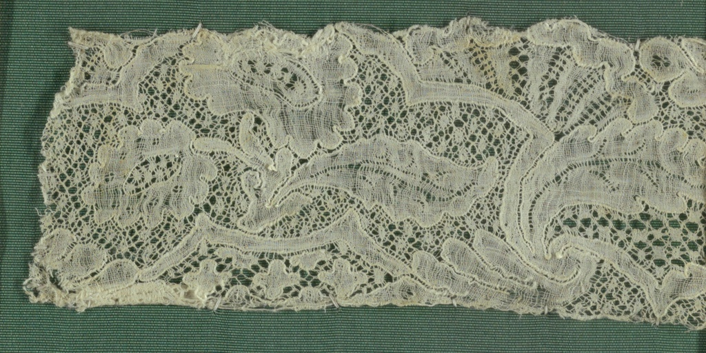 """Scalloped border fragment with """"fond de neige"""" ground. Scrolling flowers and foliage set off by solid bands."""