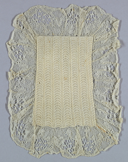 Cover with a knitted center in a scalloped design and trimmed on all four side with machine-made lace.