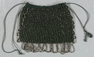 Bag of green silk netted and ornamented with steel beads. Looped fringe of steel beads on three sides; green silk drawstring at top.