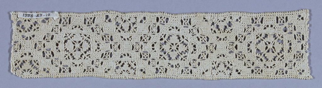 Linen band ornamented with reticella in a geometric design.