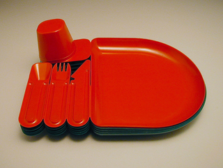 Red molded plastic unit comprising joined elements of an individual 'place setting': cup with tab handle (inverted), spoon, fork, knife and D-shaped plate; elements can be separated at joins. Disposable
