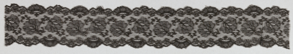 Black lace band with design of detached flowers and scallops on both edges.