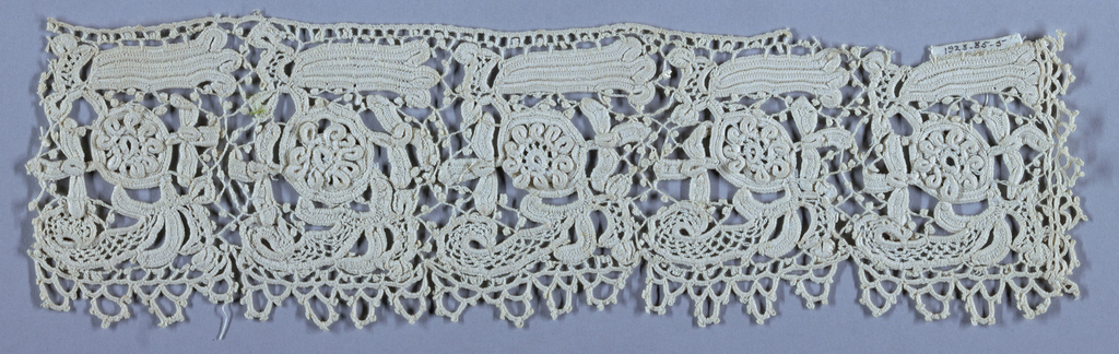 Crocheted lace border with conventionalized floral repeated five times.