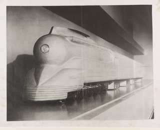 Photographic image: oblique view from the front end of the pasticine model of the first streamlined train (K-4 class), designed for the Pennsylvannia Railroad Company.