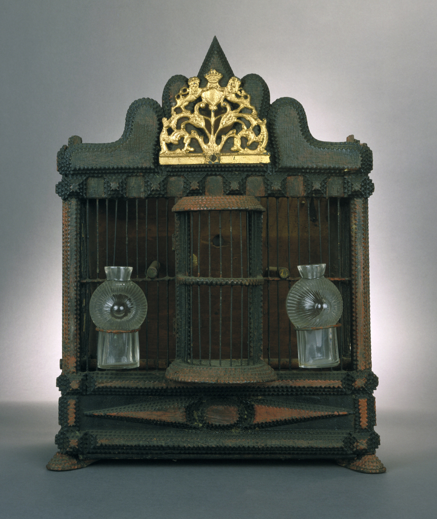 Square shaped wooden box painted black and red, with thin, vertical metal rods at front; out-curved door projecting from center, hinged on left side; two molded, clear glass bottles attached to rods on either side of door; scrolling cornice at top, with applied gold-painted metal coat of arms in center.  Woodwork has carved dentate edges and projections; two stepped, ovoid front feet, square rear feet.