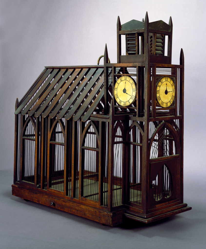 Birdcage (a) of wooden slats, dowels and metal wire in the form of a church with peaked roof; walls of clerestory-like gothic style arches; at one end a rectangular bell tower with three large, circular, painted clock faces, and door with inverted heart-shape perforation. Wood and sheet metal under tray (b) pulls out at left side.  Small loop handle of brass on roof.