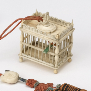 Rectangular cage (a) with turned corner posts terminating in pointed finials at top, ball feet; pierced gallery around top edges; hinged door at one side; rectangular, partitioned 'food trough' in cage, next to door;  two red and orange ivory birds sit on flat green perch suspended in cage.  Orange silk cord attached to ring at top of cage, and decorated with orange and black tassel, flat ivory bird (b), and knotted green bands near tassel.