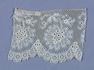 Lace in the style of Valenciennes with embroidered details.