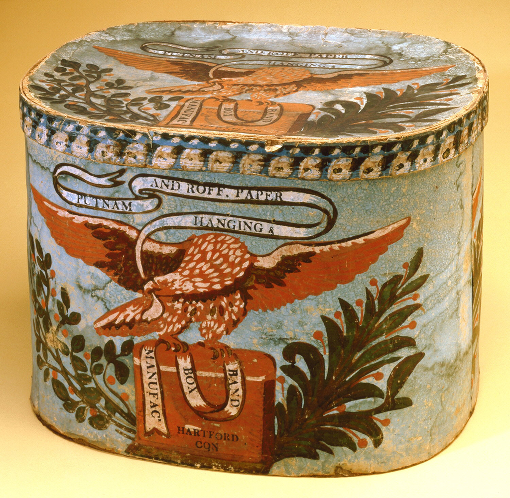 """Bandbox scene depicts eagle bearing in his beak a banderole advertising the manufacturer. Printed on banderole shown in pattern: """"PUTNAM AND ROFF. PAPER/ HANGING &/ BAND/ BOX/ MANUFACR/ HARTFORD/ CON"""". Light blue ground block printed in orange, white, gray, and light brown distemper colors, and in green, brown, black and yellow with glossy finish. Rim covered in border paper with blue ground, block-printed in white, pink, brown and green."""
