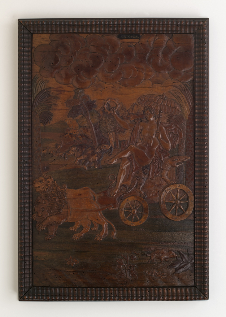 """Panel in gadrooned frame. Nude female figure, holding tambourine and feather parasol, seated in chariot with crocodile arm rests, drawn by two lions; in foreground, scaly quadruped; in background, two elephants, camel, lion and ostrich. At top right, labeled """"Africa""""."""