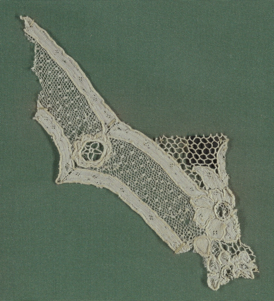 Small irregular fragment of Argentan lace from Cooper Union Lace Study Card. Square-dotted ground with a portion of a floral design.