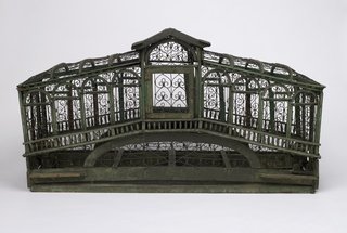 Green painted wooden frame with metal wires, modeled after the Rialto Bridge.  Intricate wire scrollwork; four doors; two feed cups; hinged panel at either end for removal of trays (trays missing).