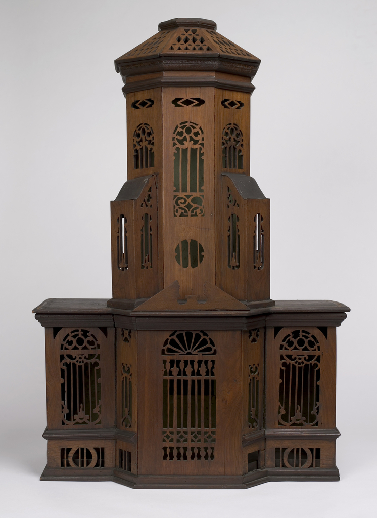 "Standing cage in form of church, with buttressed tower; door, arched windows and ornament of geometric pierced designs.  Tray (part b), opens at back; base (part c) with ""fence."""