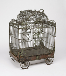 In the shape of a circus wagon, on four wheels with axles; central portion of roof arched, door and handle on each side of arch, shallow crown-like decoration and handle at top of arch; doors on long sides of cage; pull-out pan with handle on bottom of cage; decorated with looped, braided and coiled wire and tiny metal leaves.