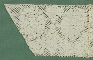 Straight-edged band with cloud like forms and scalloped areas. Round mesh. Sewn to 1897-8-9.