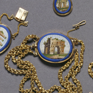 A gold oval pendant outlined in blue with an inner image of Italian architecture. Pendant is part of a set.