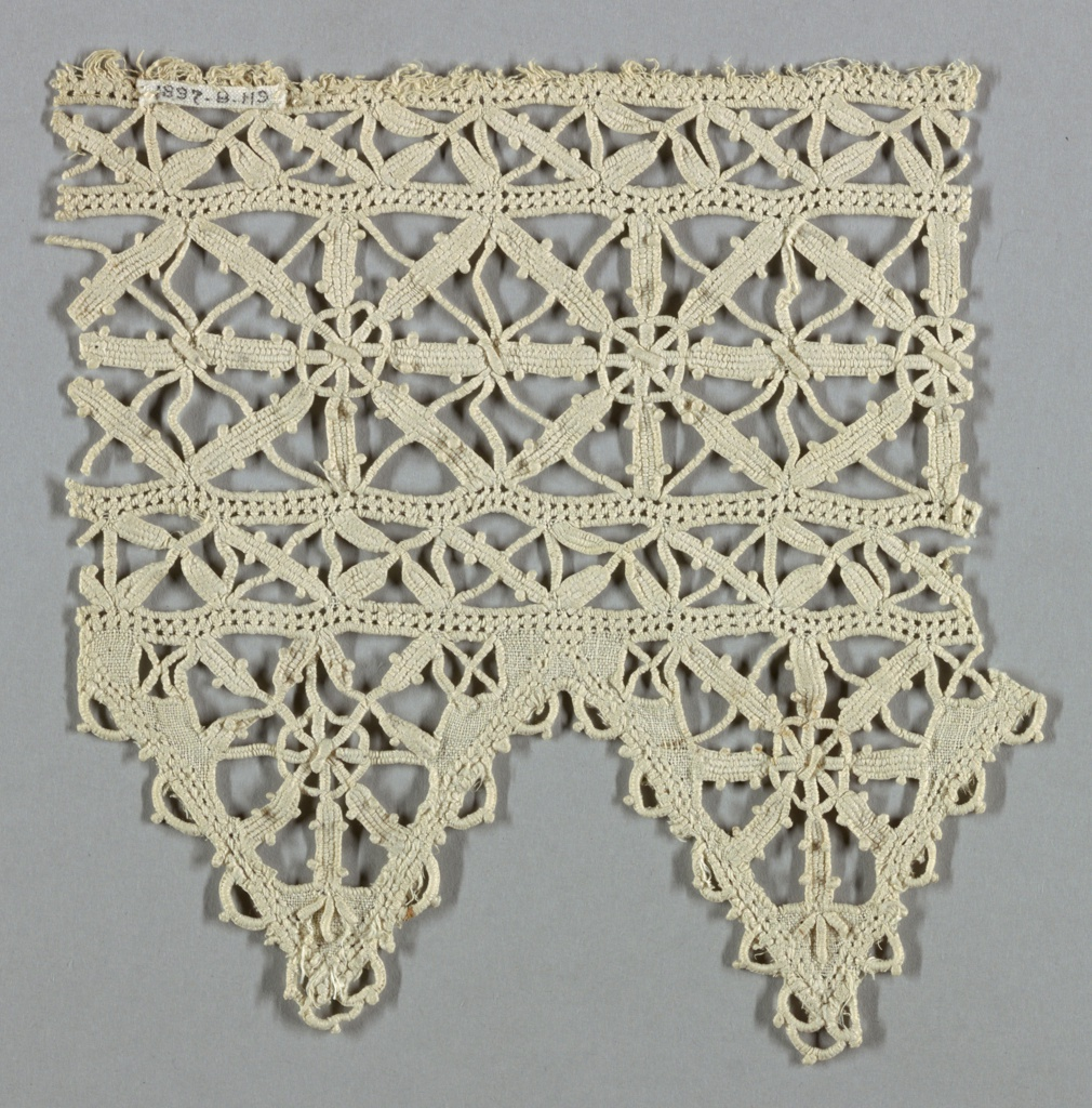 Wide panel with deep border of inverted triangles. Central panel in diamond-shaped design with tiny circles at intersections. Circle and spokes fill pointed border.