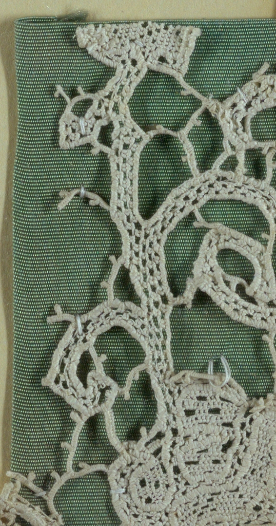 Corner fragment of flat lace in a floral design. Fragment is mounted on a fabric-covered board and framed behind glass. Frame is natural wood.