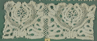 Lace fragment in a scrolling tape pattern with details in Genoese seed stitch. Fragment is mounted on a fabric-covered board and framed behind glass. Frame is natural wood.