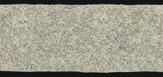 Band of Binche-style lace worked with a compact floral design. Edges straight and ends fringed.