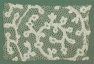 Cut fragment with scrolling vine motif. Previously mounted on a fabric-covered board for study.