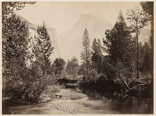 Landscape featuring wooded area, river, and mountains in the background.
