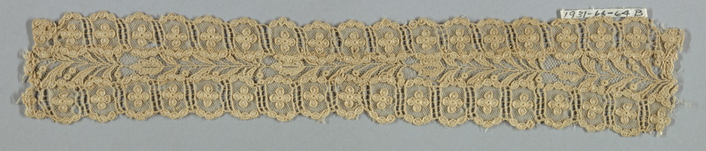 Beige imitation Alençon. Ornamental strip made up of small pieces of lace, for the center a stem with leaves with a border on either side in design of four-petaled flower in compartments.