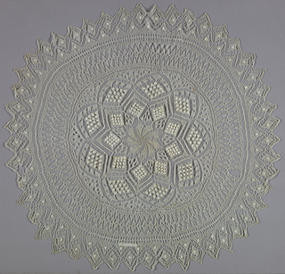 Circular cover knitted in a design of diamond-shapes and other lace-inspired forms. Sawtooth edge.
