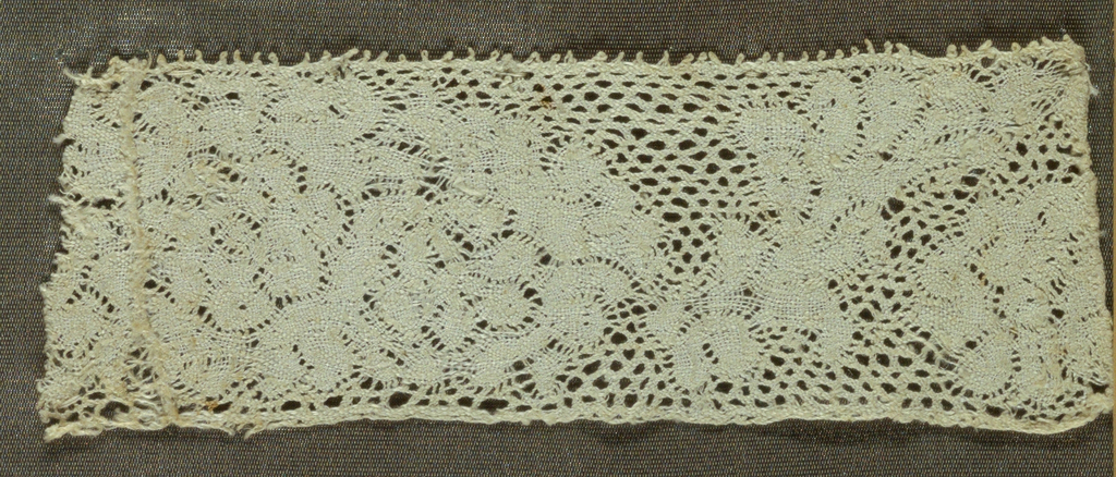 Narrow straight-edged border with a large, solidly massed floral design.