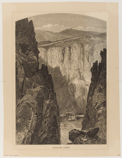 View of canyon, high cliffs on each side, snow-covered mountains in the background.