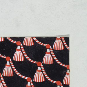 On black background, red and white striped tassels suspended from striped roping placed on a diagonal.