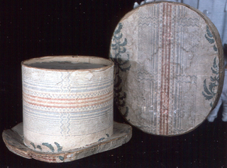In the shape of a top hat; covered with striped paper in white, gray and red, with portions of foliage stripes.