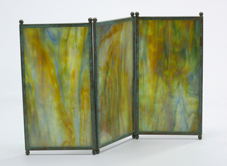 Screen consists of three vertically rectangular panels of marbleized glass, each panel framed with narrow copper edging oxidized to green and orange-red tones with two small ball feet at each end. The panels are hinged together by means of wire at juncture of feet and screen. Glass marbleized in tones of blue, yellow, green and red.