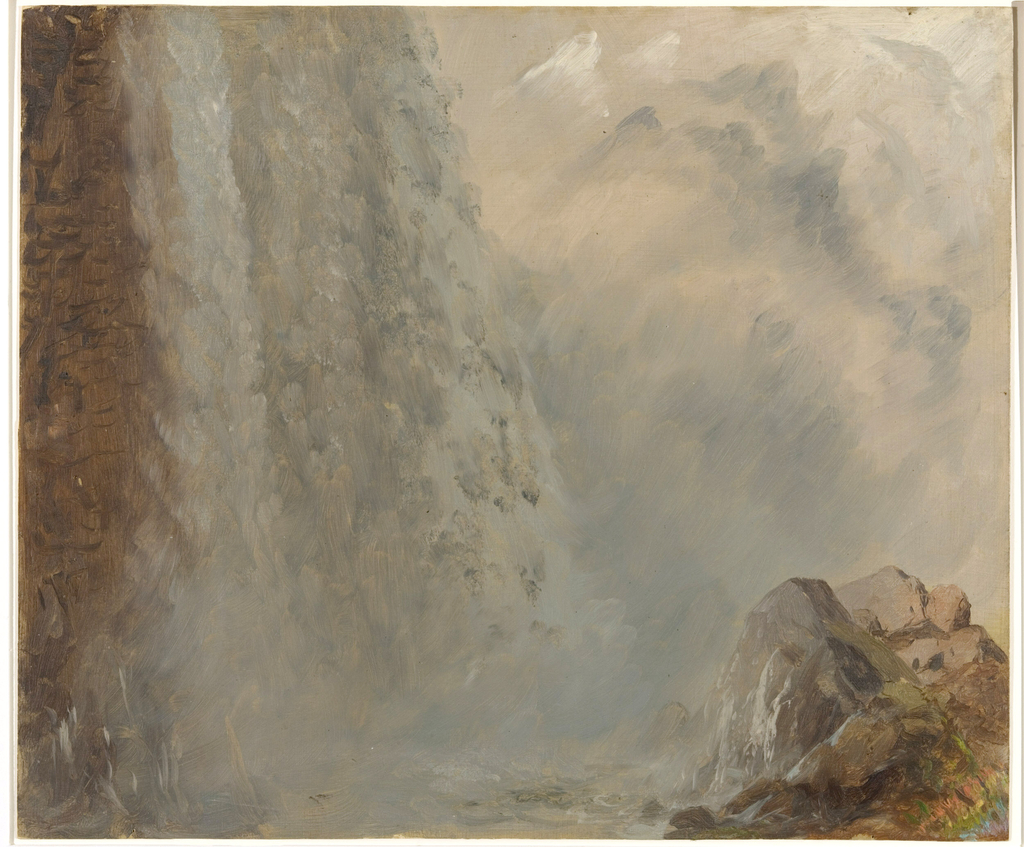 Horizontal view of the base of the Falls, shown at left, partially obscured by mist and spray, with rocks in right foreground containing indications of a rainbow coloring.