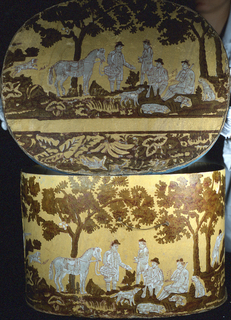 A group of four hunters with dogs and a horse shown within a clearing in the woods. Printed in pink, white and what was probably green on a yellow field. This same design appears on the lid.