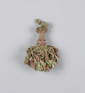 Skirt of pink, white and green silk threads, twisted and looped, and each supporting a tassel of its own color. Head is vase-shaped and wrapped in pink, white and green threads in a chevron pattern. Collars are formed by looped threads at the top and bottom. Cord of braided silk threads.