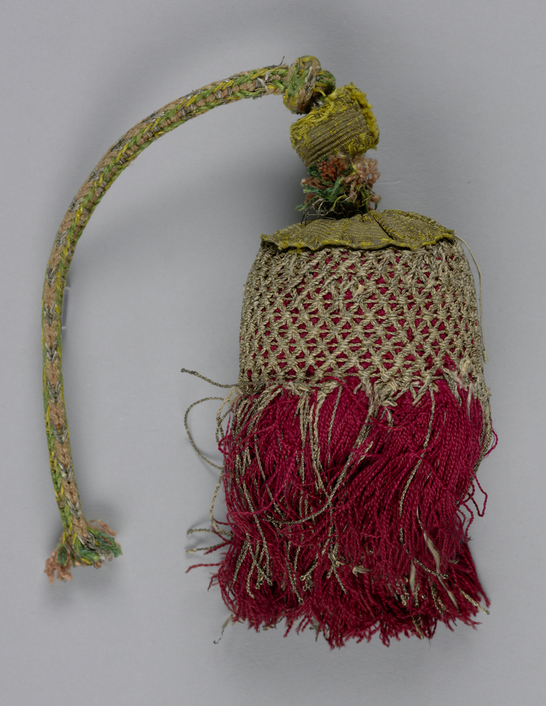 Over a linen core, a skirt of red silk partly covered by a trellis of silver thread and topped with a galloon (probably a later addition). Cord of knotted pink and green silk and silver thread with a knob of galloon (later addition).