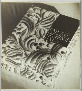 The black and white photograph depicts the cover of a box intended to hold stationery, in a foliate design. The object is positioned on the diagonal in the photograph. In the upper right hand corner, the company and product names, Eaton's/ Highland/ Linen, are imprinted in white capitals in a serif-style type, with a justified left margin, in the lower half of a black rectangle.