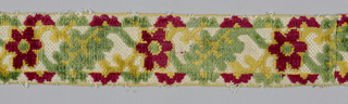 Narrow bands of trimming with crisscrossing leaf and flower design with guard borders of half-circles in cut pile of red, green, and yellow on a white foundation.