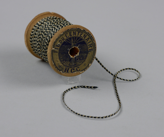 "Narrow tan, white and black silk braid wound onto a wooden spool. Paper label on one end: ""Fil du Centenaire. H.C.C."""