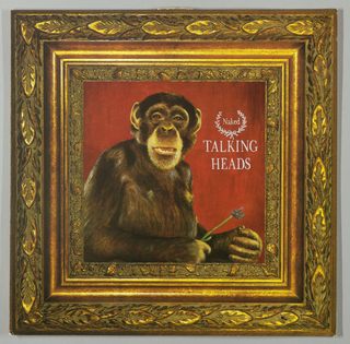 Recto: The central feature of the design is a reproduction of a portrait painting of the head, upper body and arms of a chimpanzee, positioned toward the left against a deep red background within an ornately carved, two inch gold frame, also reproduced from the original.  The area around the subject's partly opened mouth is highlighted and he appears to be smiling. His eyes are shining. He holds a small purple flower on a green stem, extending upward to the right, in his right hand. The fingers of his left hand are bent toward his right. To the right of the chimpanzee's head is a laurel wreath, open at the top, with the album title in small upper and lower case letters imprinted within. Talking Heads in somewhat larger capitals is centered below. Verso: Natural light, its source not seen, picks out highlights in the photographic background of dense vegetation and a still body of water, as well as in the zigzag arrangement of the song titles, one to a line. These are imprinted in small capitals beginning in the center, about a third of the way down from the top edge, and continuing into the lower third.